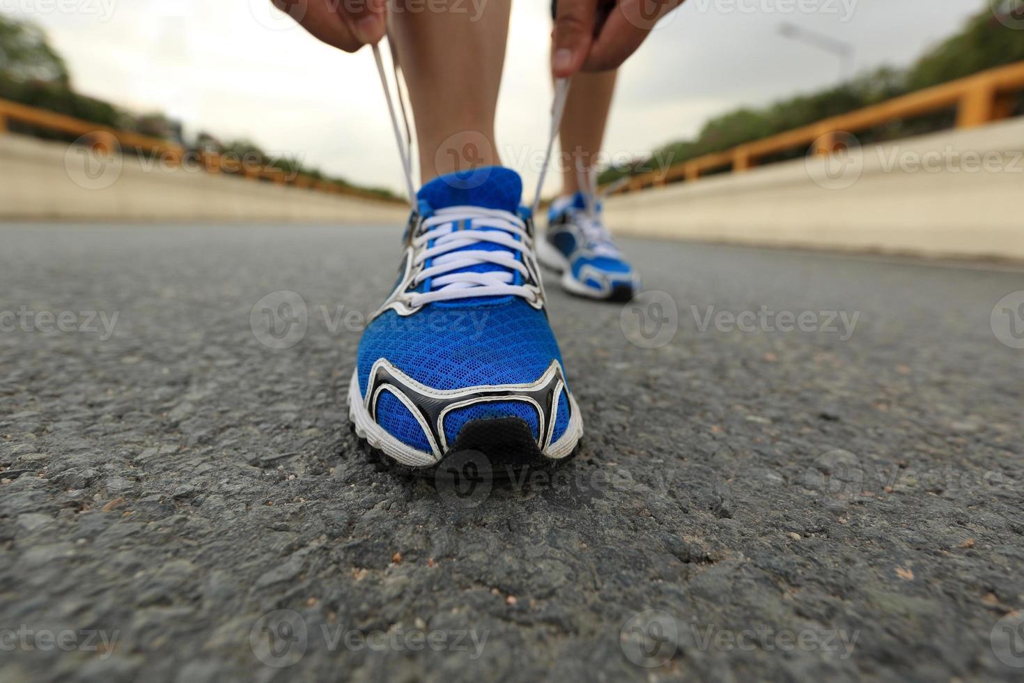 löpare för ung kvinna som knyter skosnören på stadsvägen foto