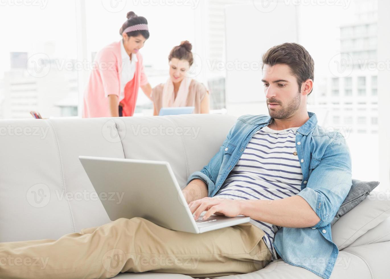 fokuserad affärsman som använder bärbar dator på soffan foto
