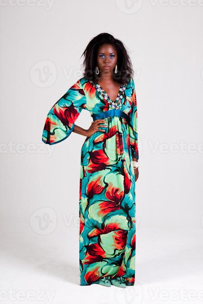 attraktiv ung kvinna i en färgglad lång klänning foto
