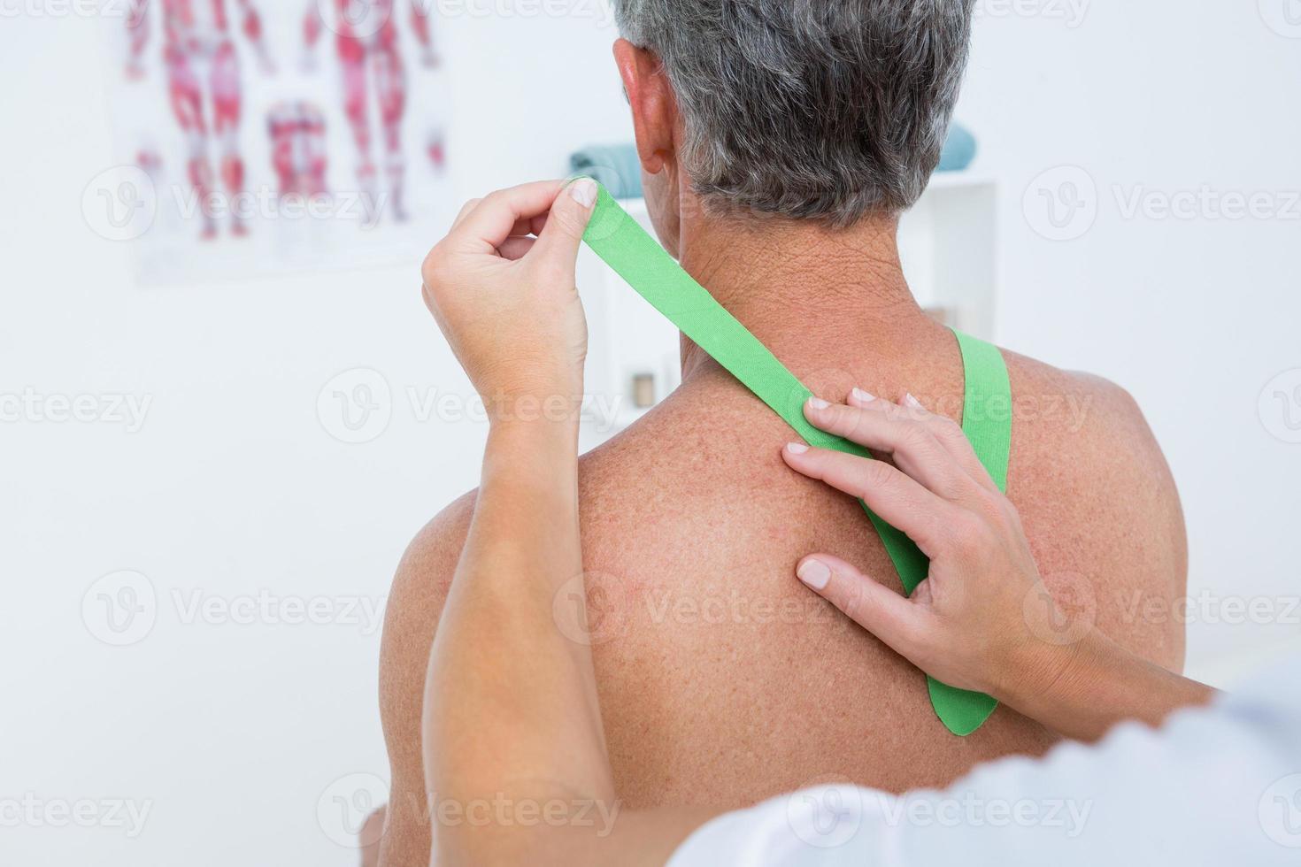 läkare undersöker hennes patientens axel foto