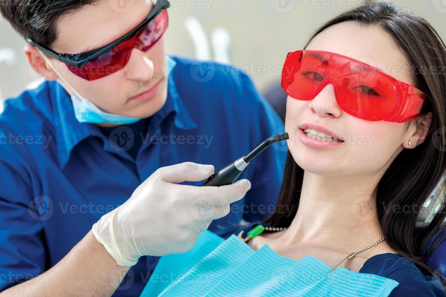 tandprocess. tandläkare som håller en ultraviolett lampa i munnen foto