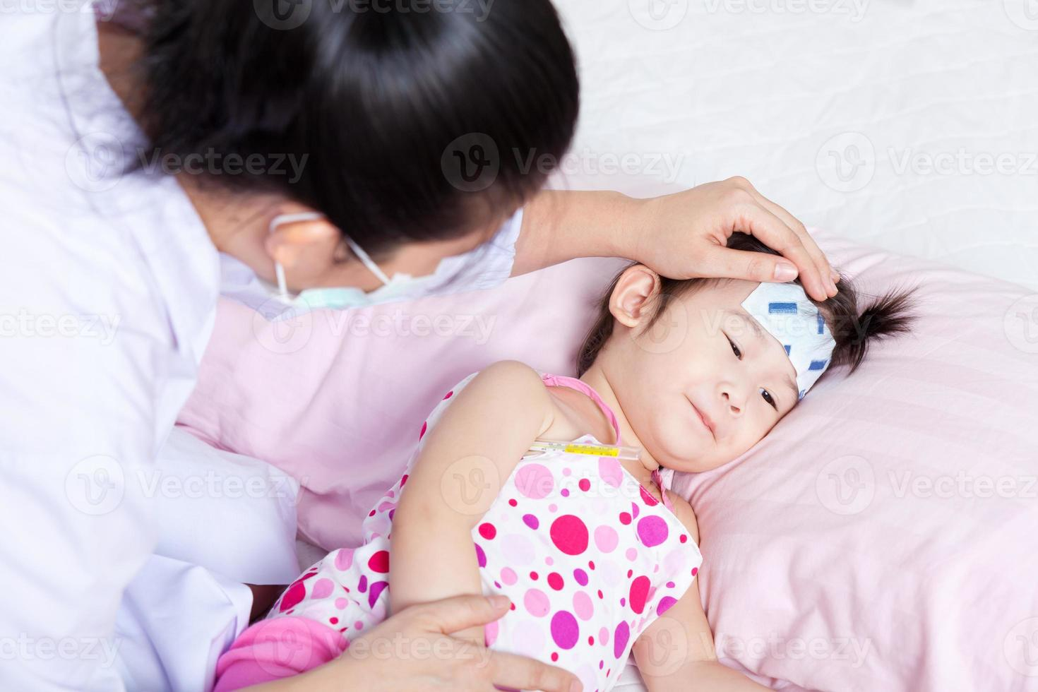 sjuk liten flicka som vårdas av en barnläkare foto