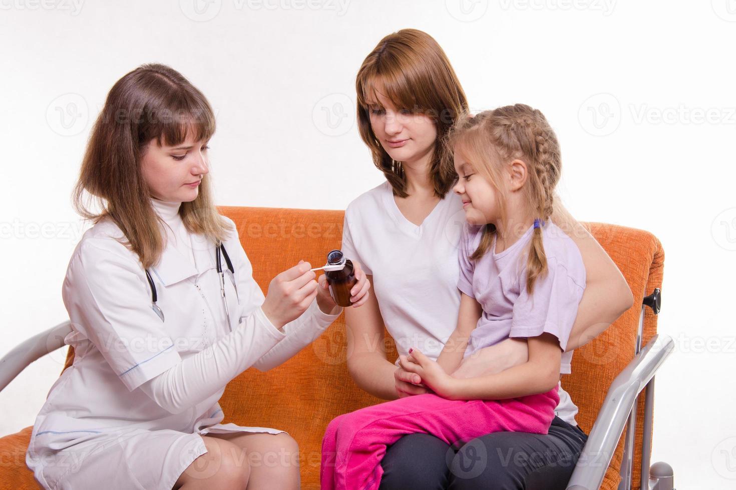 barnläkare kommer att ge sjukt barn sittande mor medicin foto