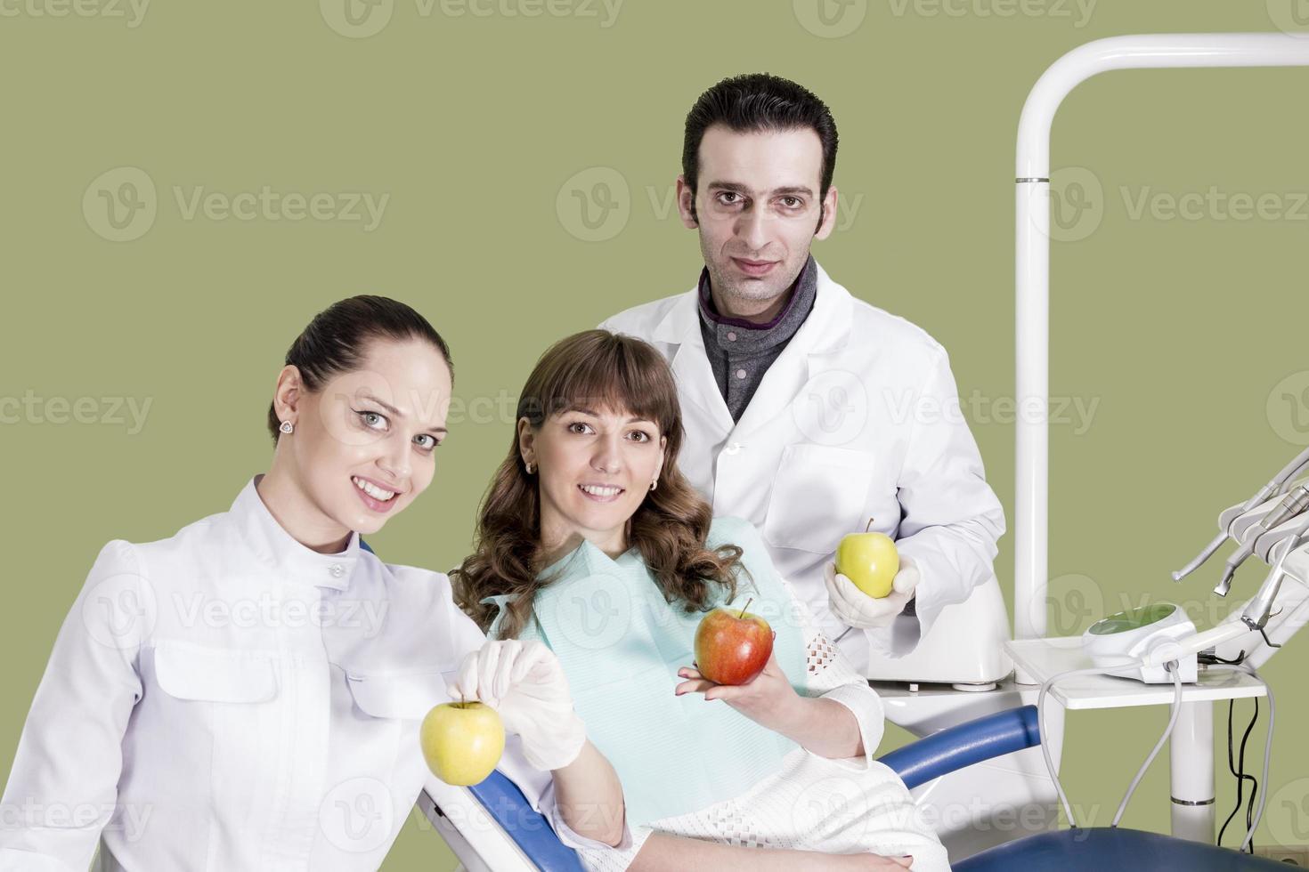 assistent tandläkare och patienten håller i hand av äpplet foto