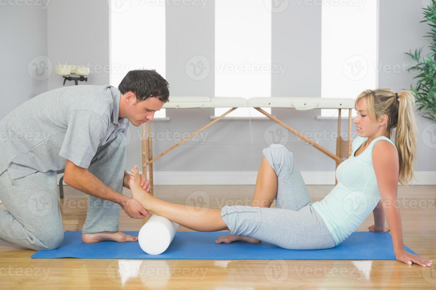 fysioterapeut som undersöker patientens fot medan man sitter på golvet foto
