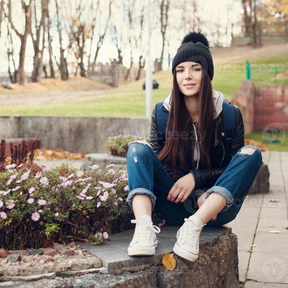 tonåring flicka sitter på trappan mot grunge väggen foto
