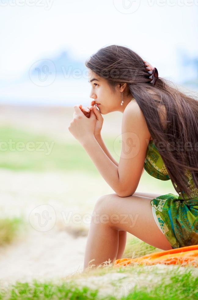 vacker biracial tonåring tjej som sitter på tropisk strand och ber foto