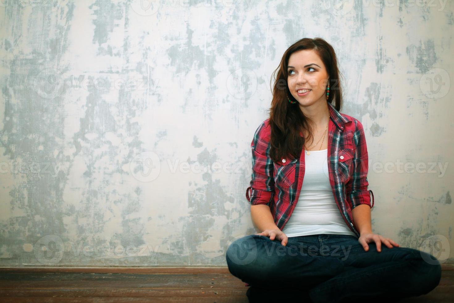 flicka sitter på golvet korsar reparationer foto