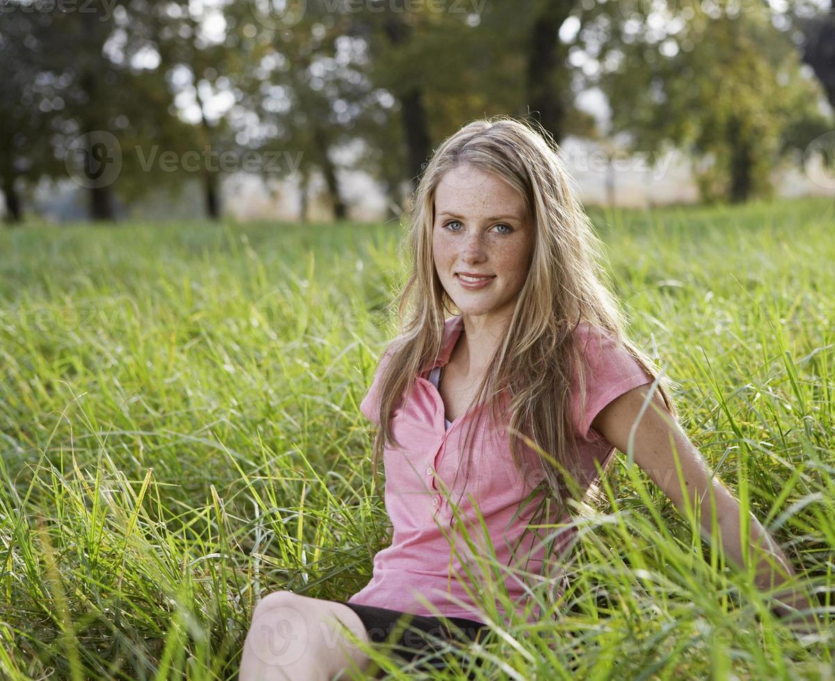 tonårsflicka sitter i fältet foto