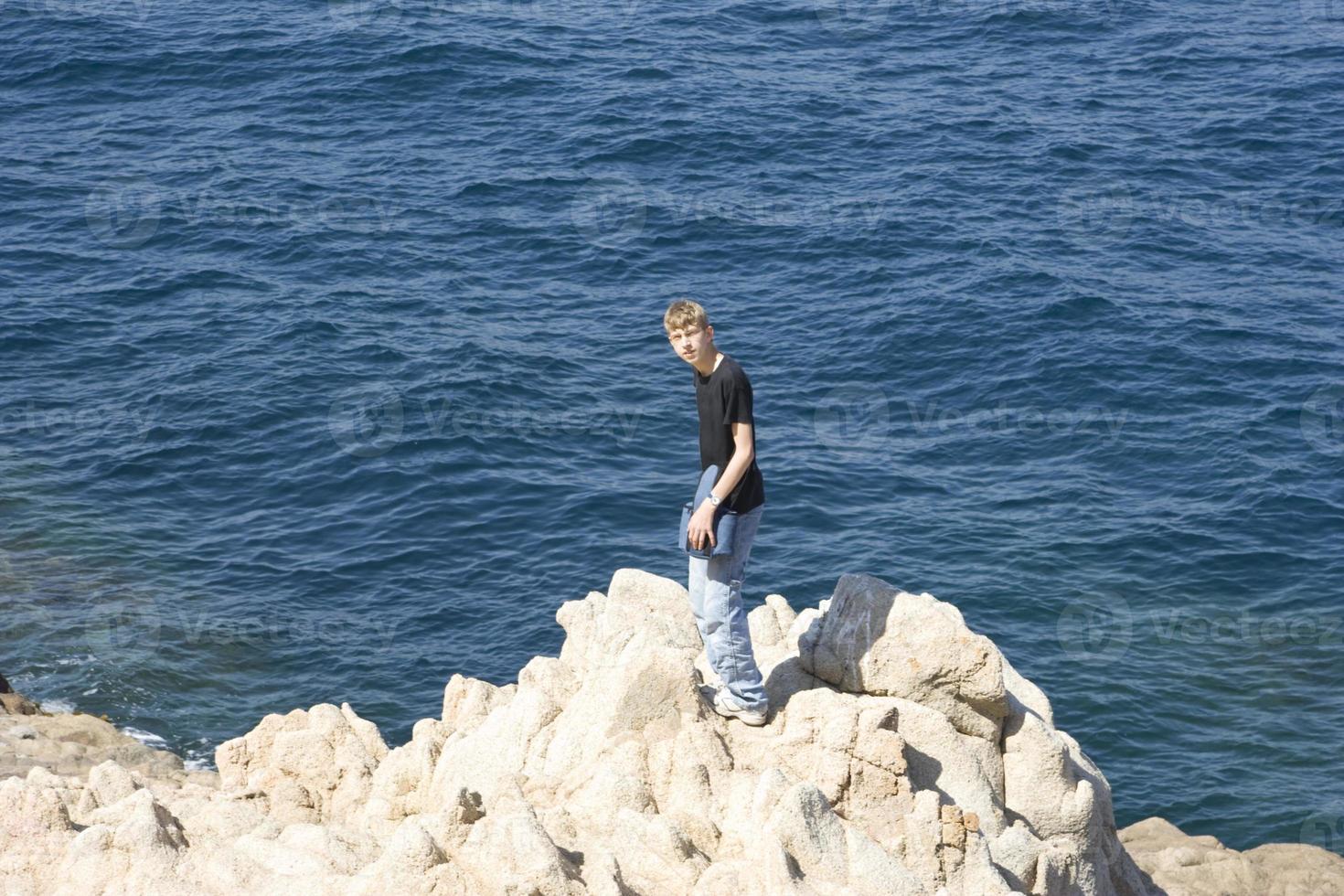 tonåring står på klippor foto