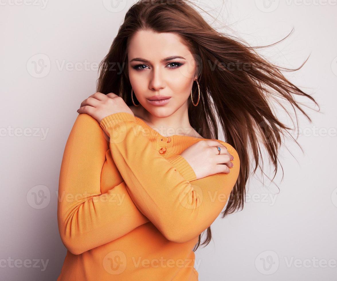 ung skönhetsmodell tjej iin casual orange tröja. foto