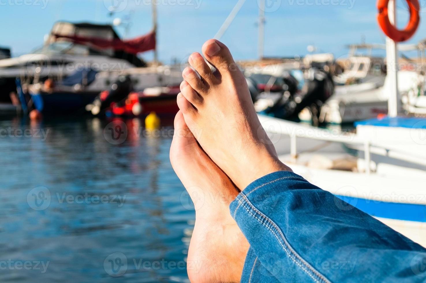 manliga fötter mitt emot havet foto