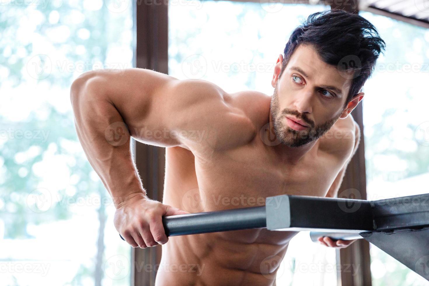 manlig kroppsbyggare träning på parallella barer foto