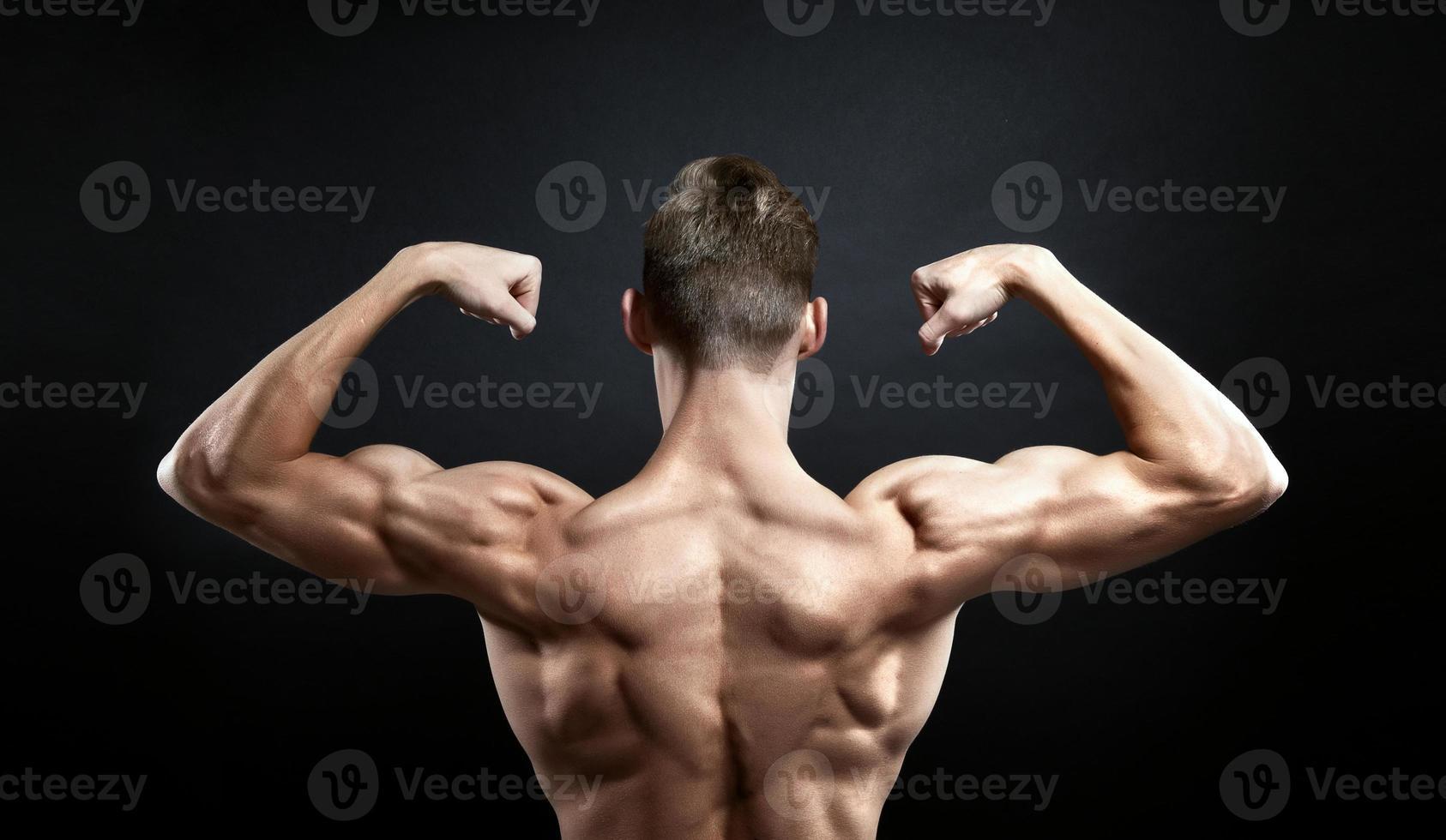 muskulös manlig tillbaka på svart bakgrund foto