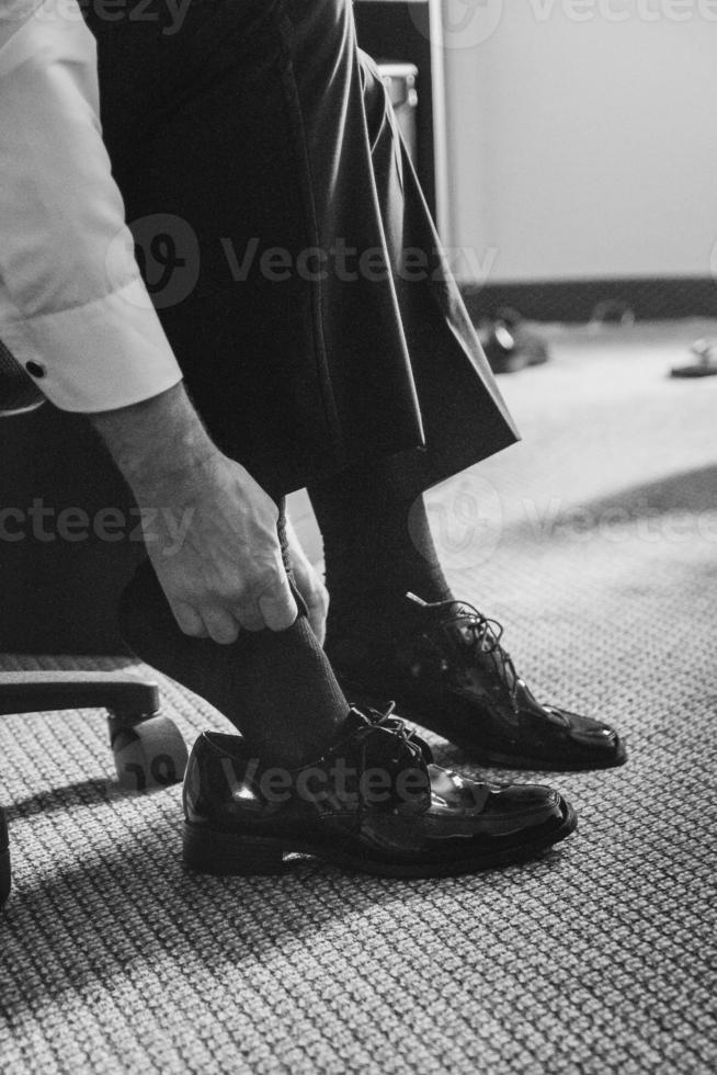 manlig hand som tar på sig formella skor foto
