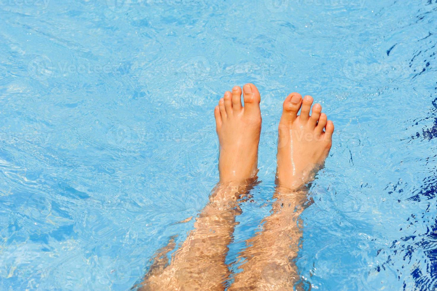 manliga fötter flyter på vattnet foto