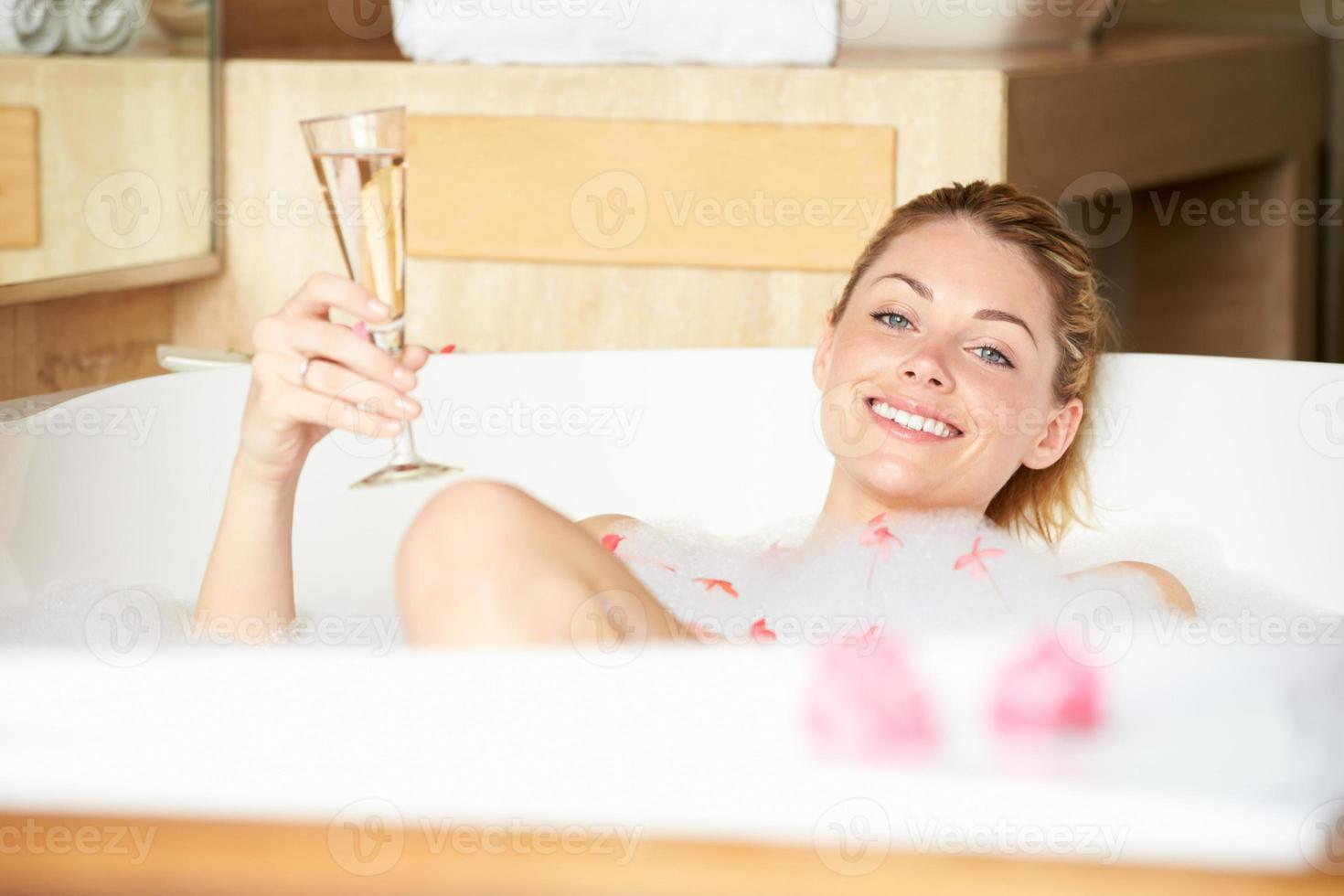 kvinna kopplar av i badet dricker champagne foto