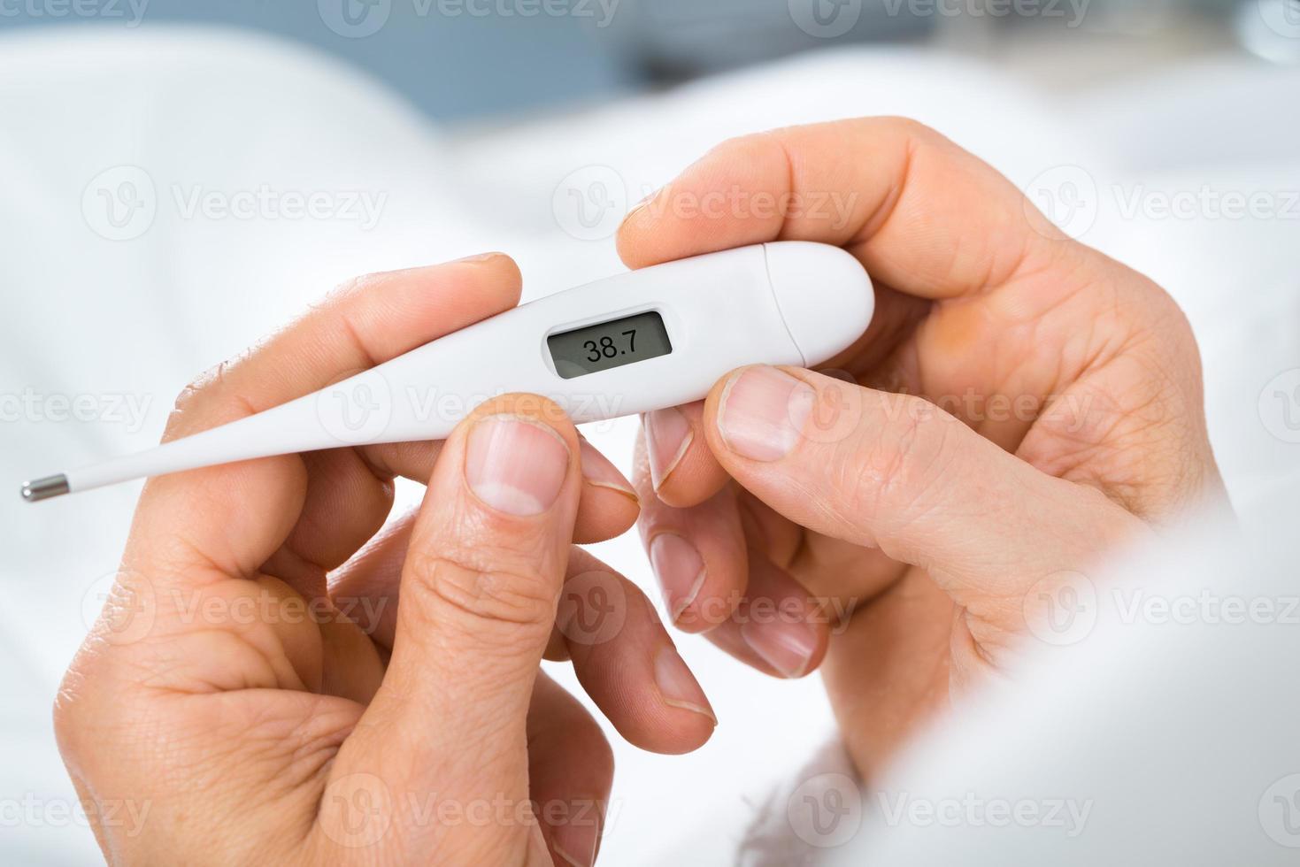mans hand som håller termometer foto