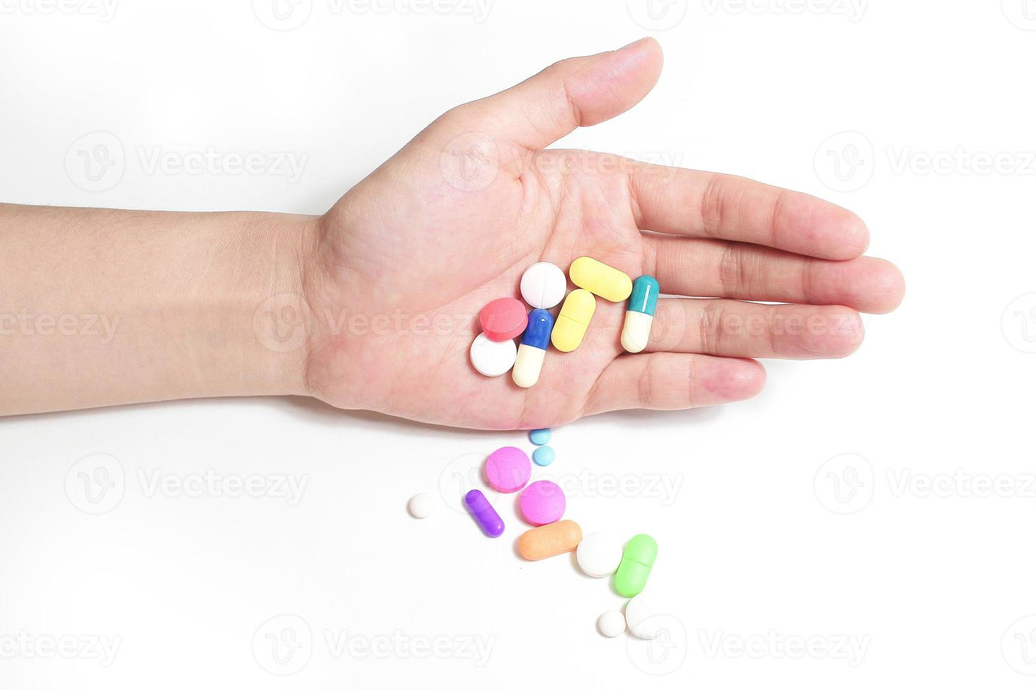 handen håller många mediciner, lådor med mediciner i bakgrunden foto
