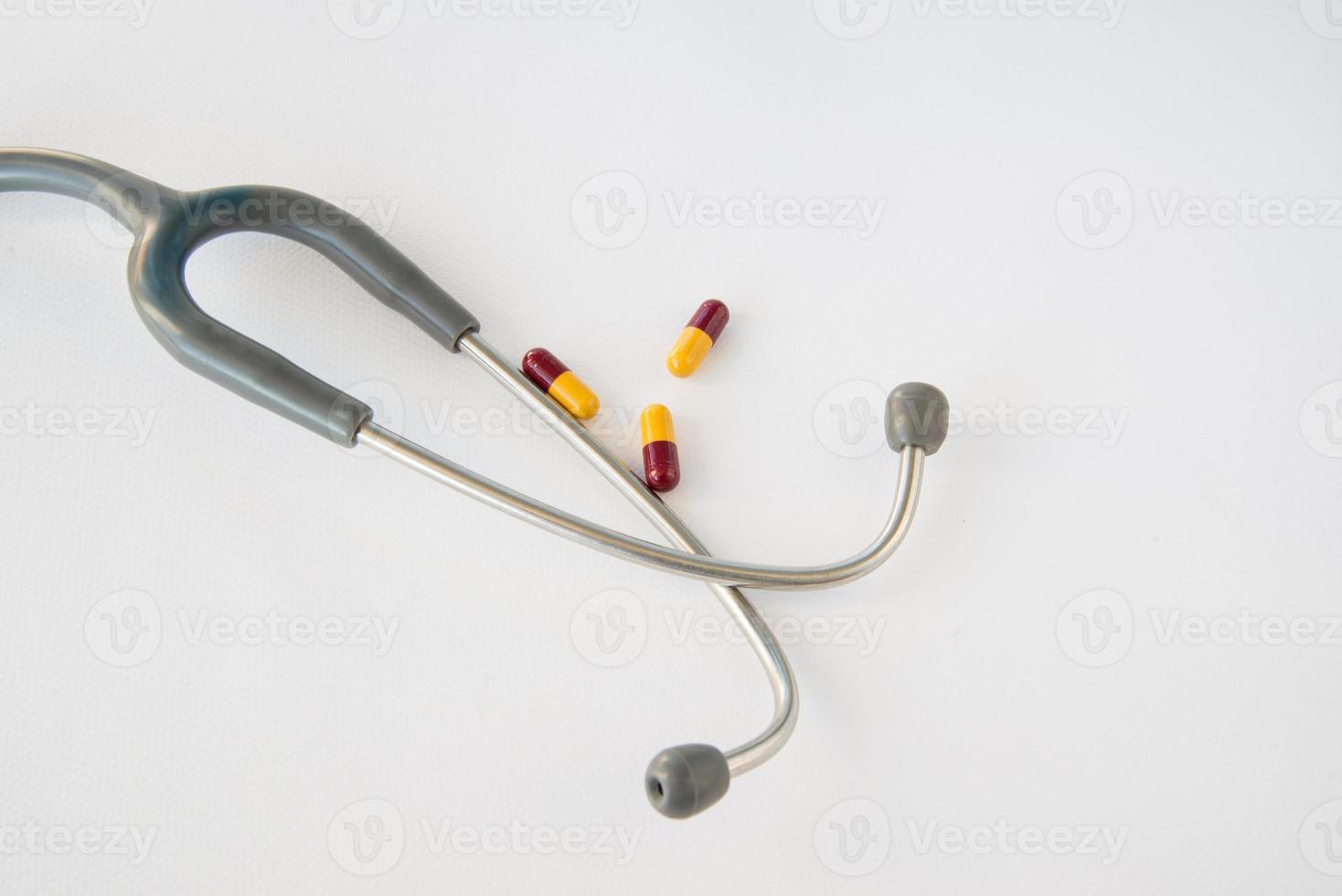 stetoskop och piller på vit bakgrund. foto