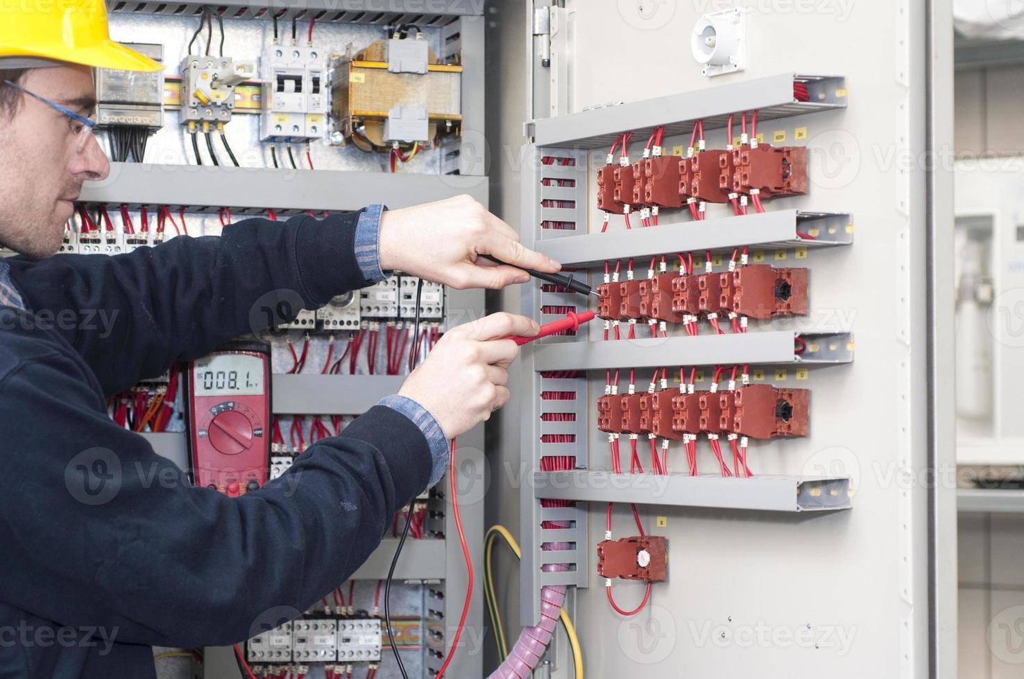 elektriker som testar industriell maskin foto