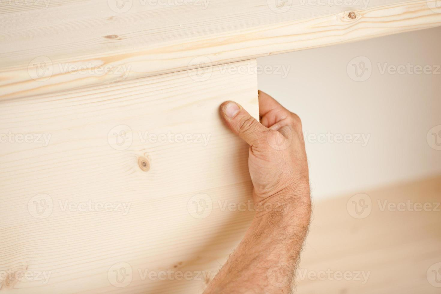 hand att placera träplatta på plats foto