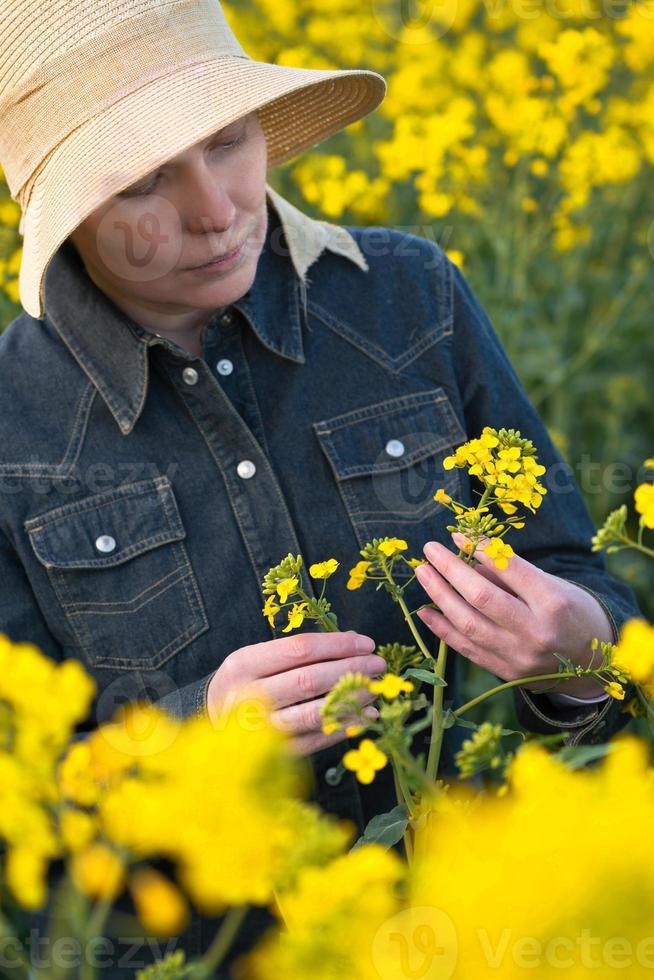 kvinnlig jordbrukare i rapsfrö odlat jordbruksfält foto