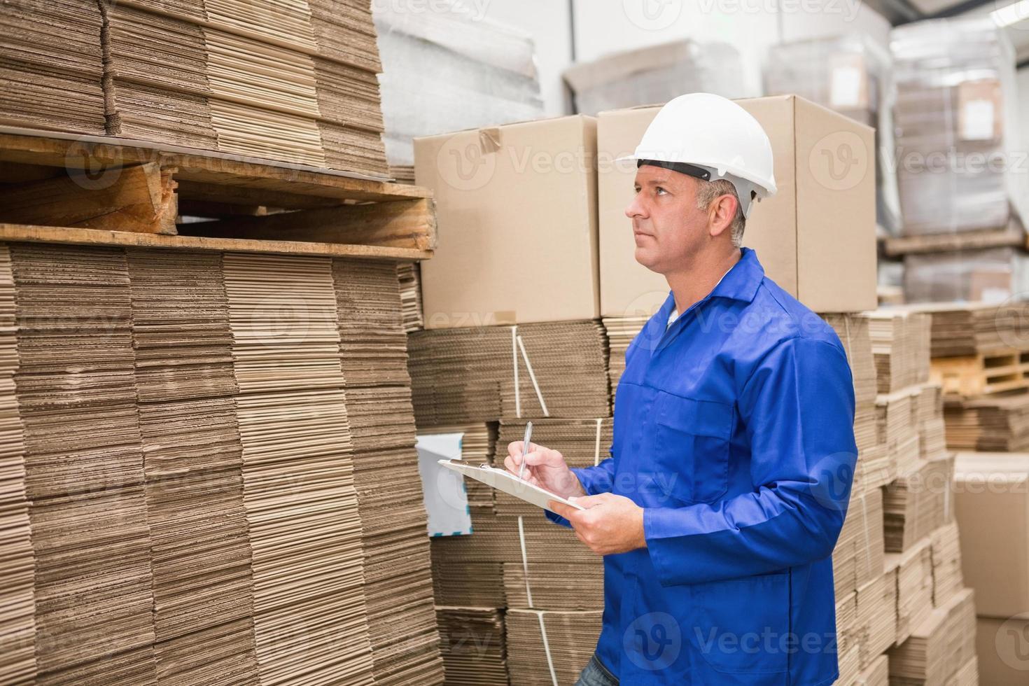 lagerarbetare som kontrollerar sin lista på urklipp foto