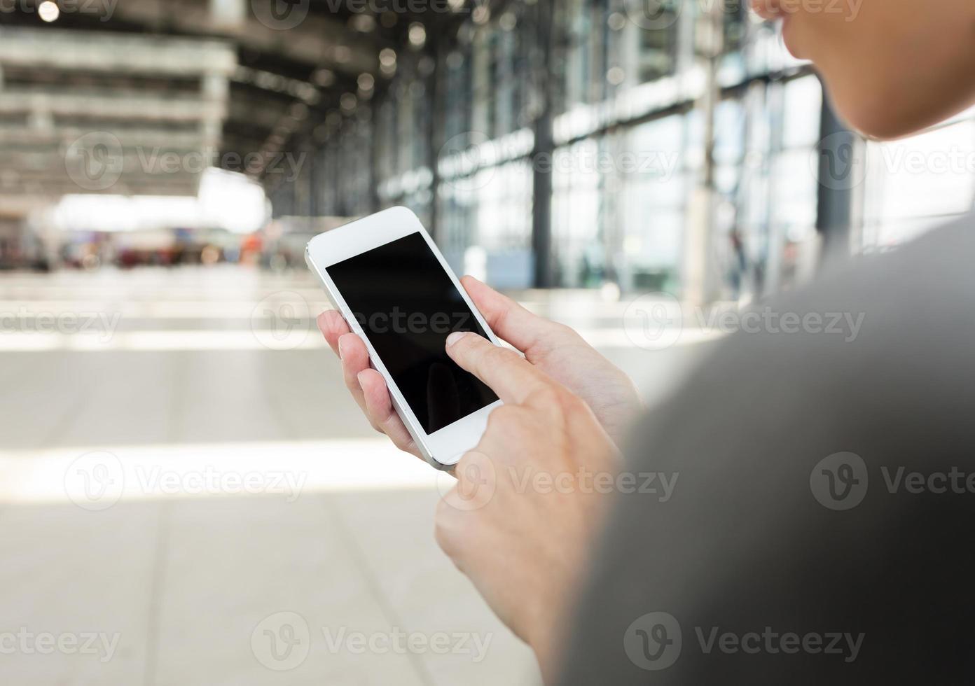 använda smarttelefon på flygplatsen. foto