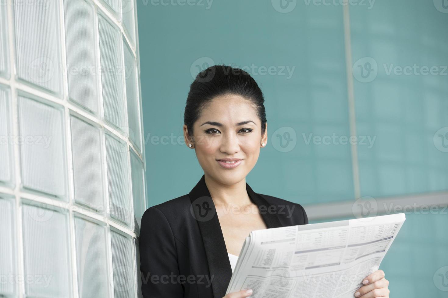 kinesisk affärskvinna som läser tidningen foto