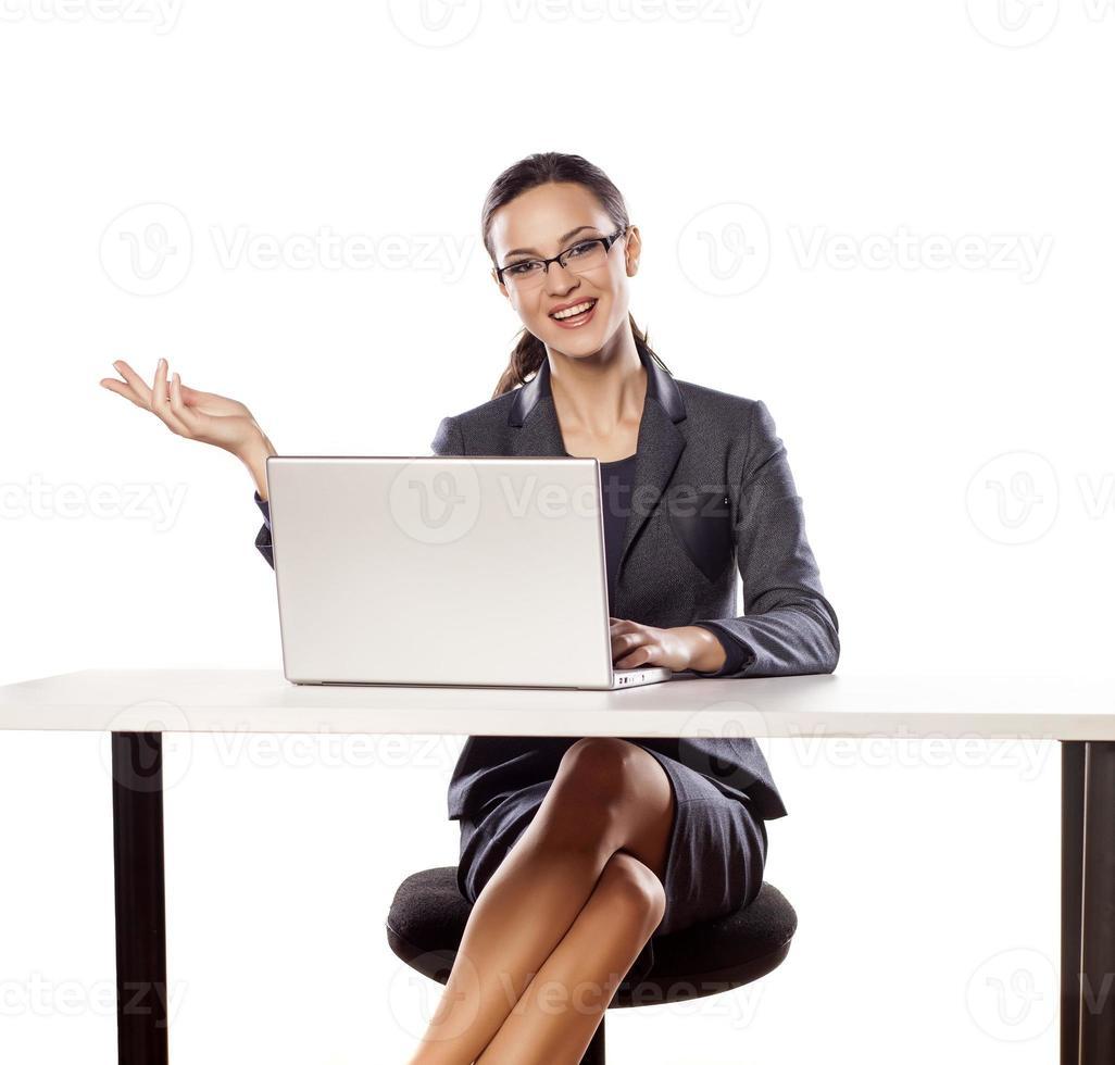 le affärskvinna som sitter vid bordet med laptop foto