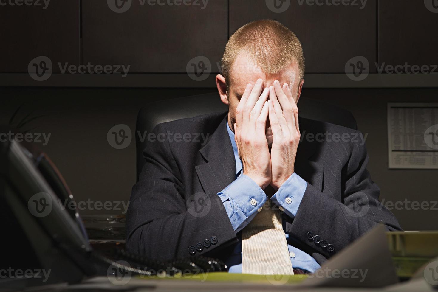 affärsman med huvudet i händerna foto