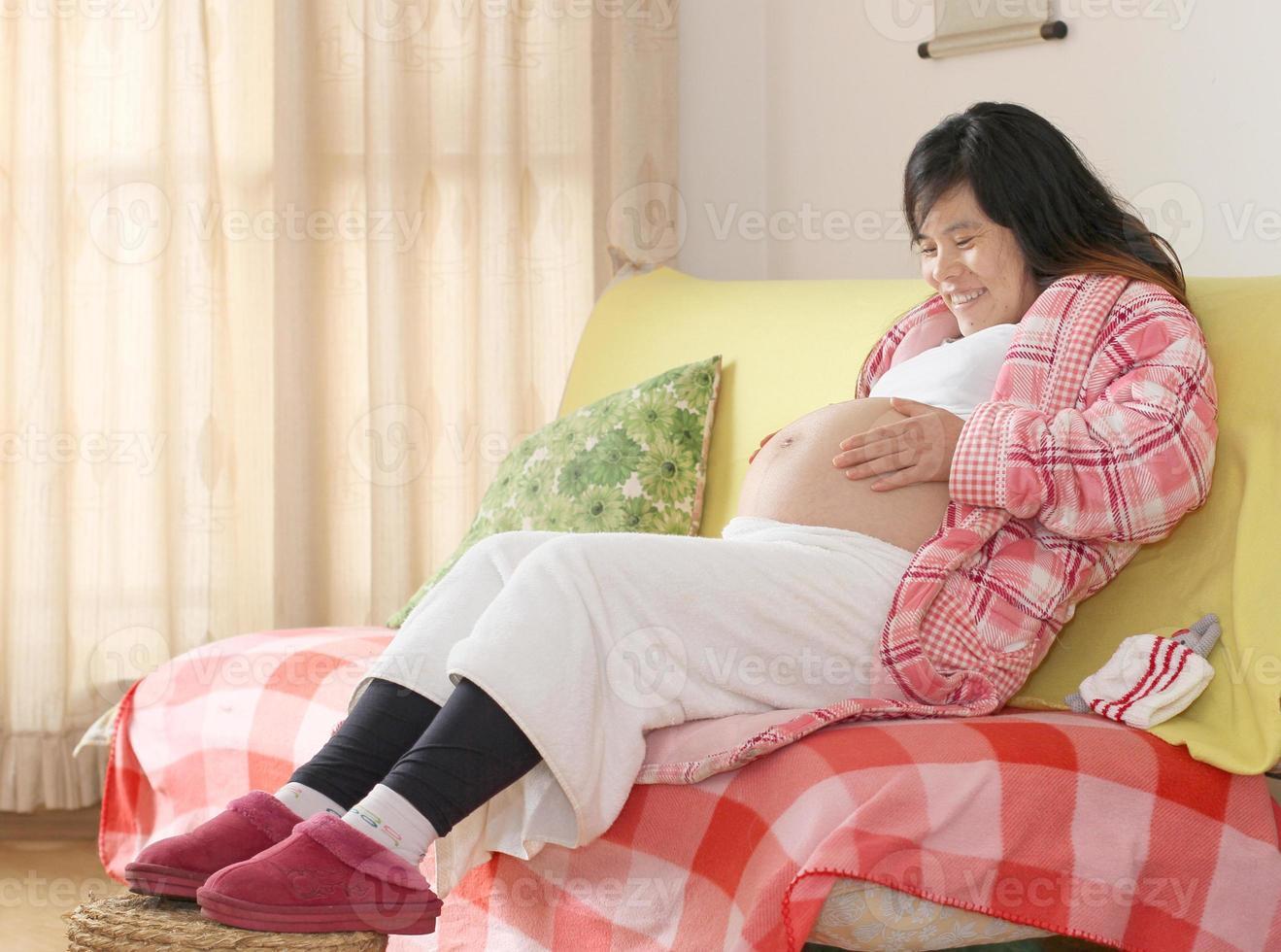 gravid kvinna sitter på soffan foto