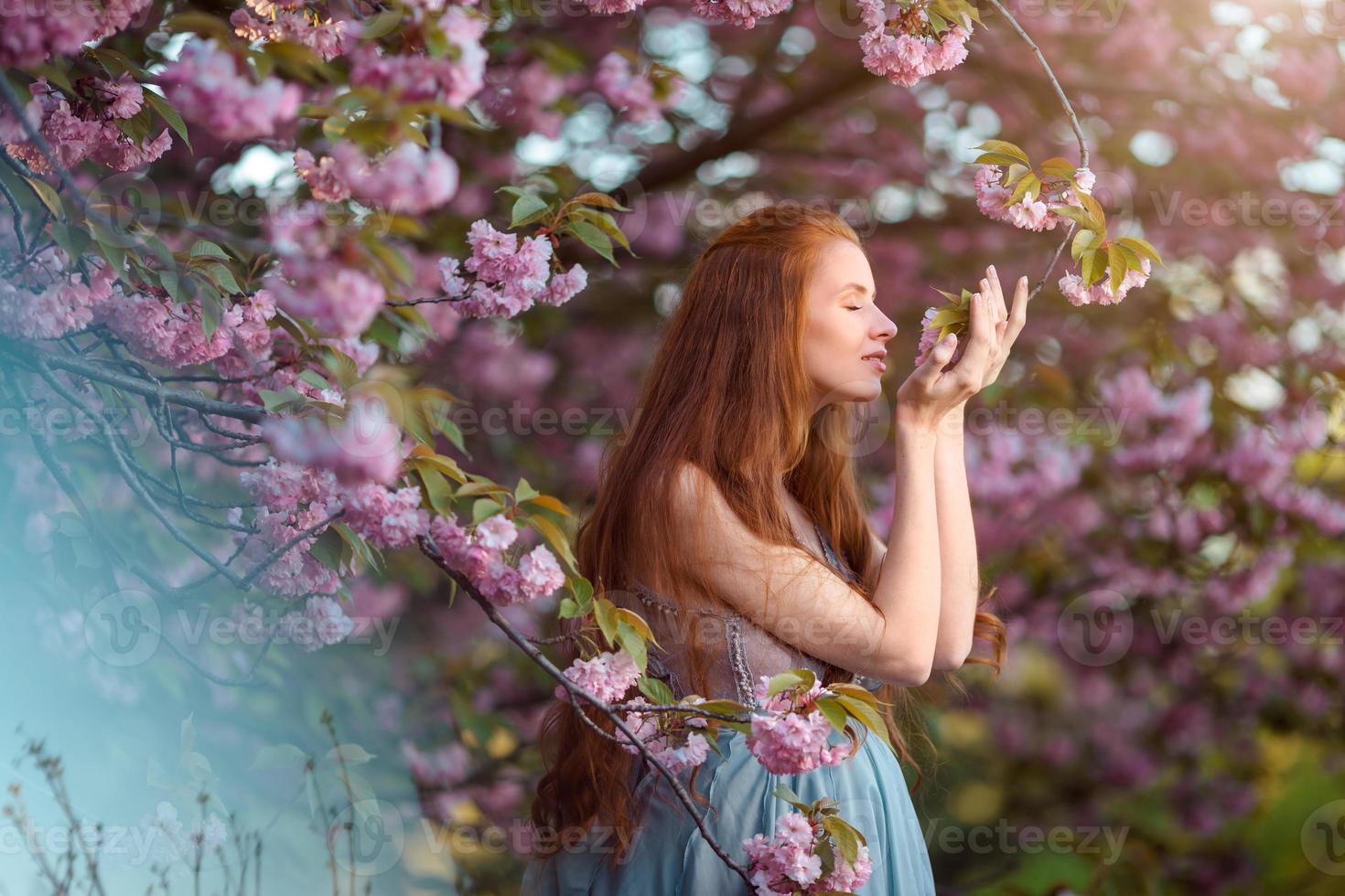 vacker gravid kvinna i blommande trädgård foto