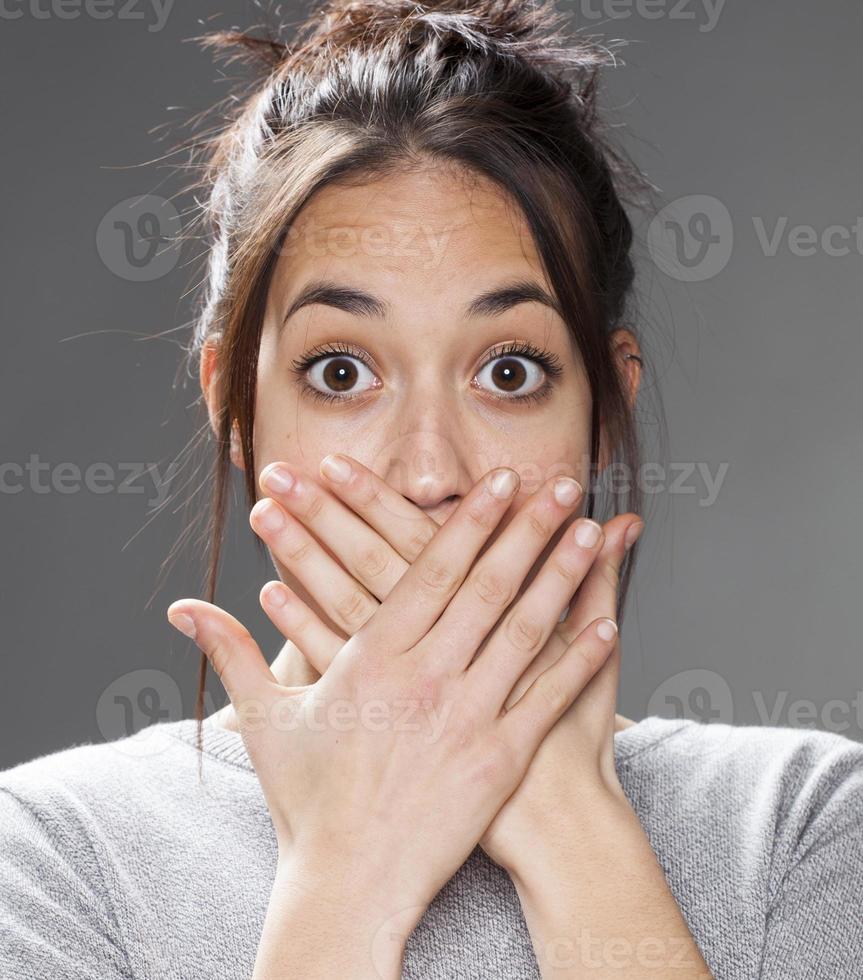 mållös 20-talets multietniska tjej med händerna på munnen foto