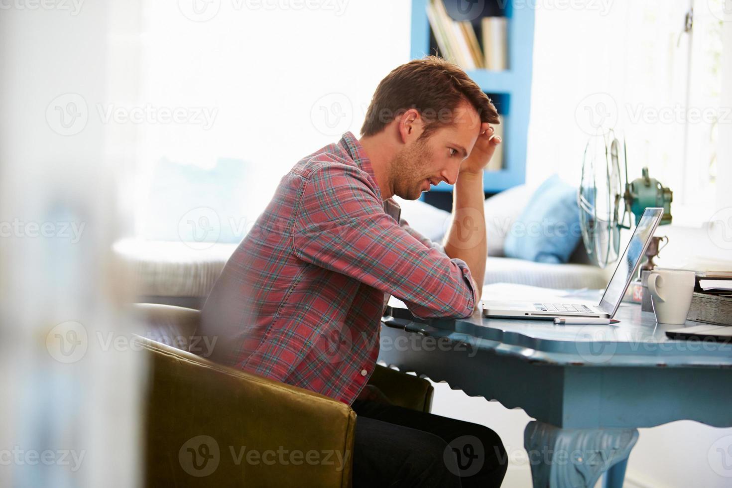 stressad man vid skrivbordet på hemmakontoret med laptop foto