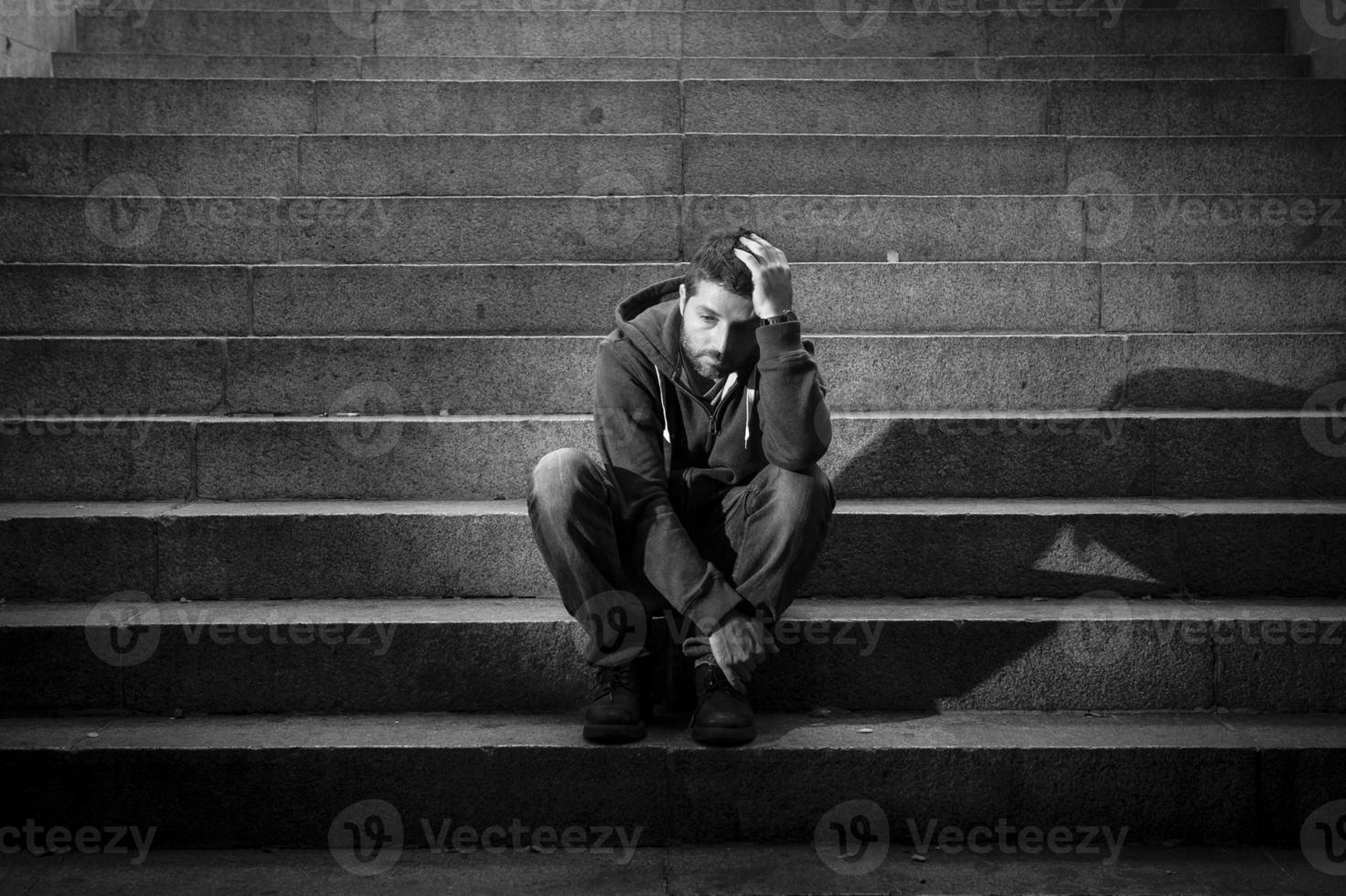 ung man lider av depression sitter på botten gatan betong trappor foto