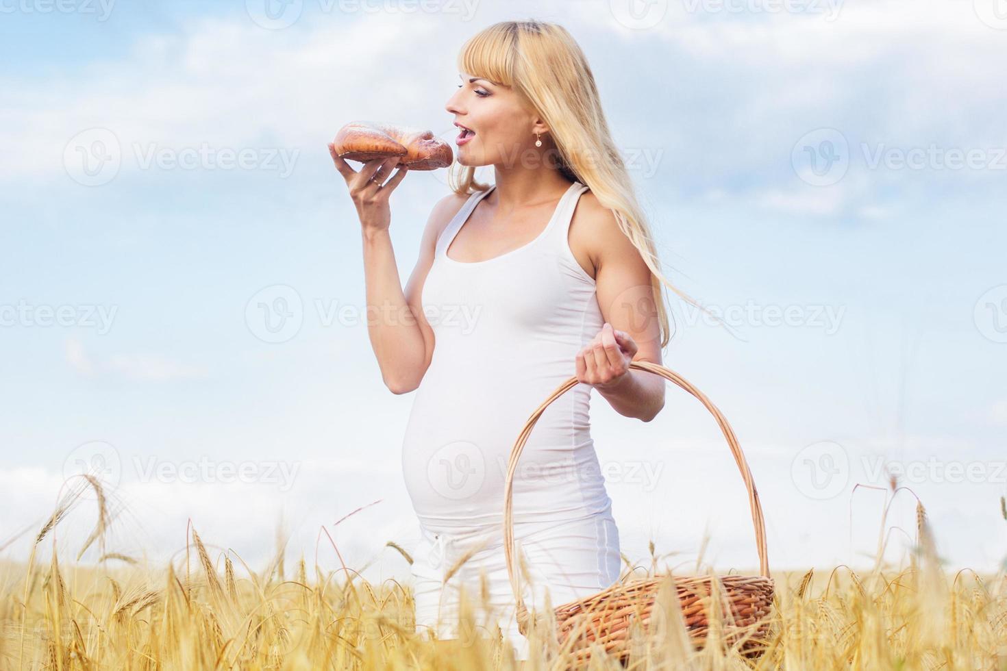 gravid tjej i rågfält med korg med färska bullar foto