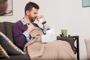 man kämpar förkylning hemma foto