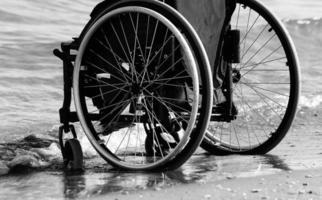 rullstol bredvid havet på sandstranden foto