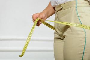kvinna som mäter hennes höfter med tejp foto