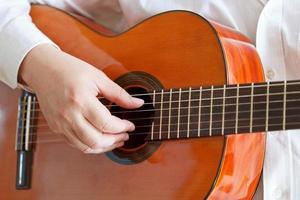 man spelar på klassisk modern gitarr