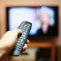 titta på tv och använda fjärrkontrollen foto