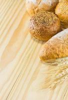 bröd och vete på träbakgrunden, varm toning, selektiv foto