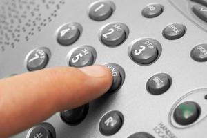 finger- och telefonens knappsats foto