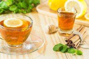 te med mint honung kanel och citron på trä bakgrund foto