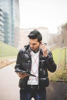 ung indisk affärsman anordnar teknologiska enheter foto