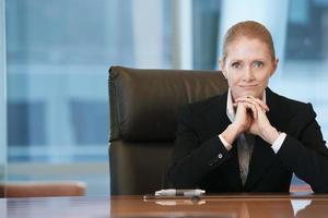 säker affärskvinna vid konferensbordet foto