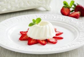 jordgubbsblancmange garnerad med färsk jordgubbe foto