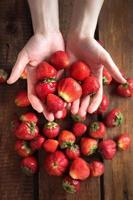 hand i hand som håller jordgubbar foto